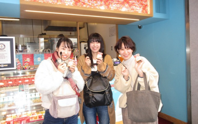 画像:店の前でポーズを取る女学生